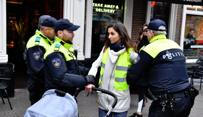 A Netherlands woman pushing stroller, wearing a yellow vest, who failed to produce ID & remove vest was arrested